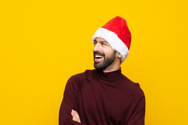 Mann mit weihnachtshut über der lokalisierten gelben wand glücklich und dem lächeln