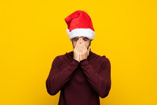 Mann mit weihnachtshut über getrenntem gelbem hintergrund mit müdem und krankem ausdruck
