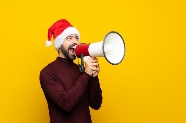 Mann mit weihnachtshut über lokalisierter gelber wand, die durch ein megaphon schreit