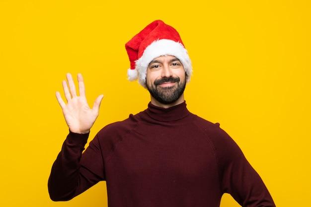 Mann mit weihnachtshut über lokalisierter gelber wand, die mit der hand mit glücklichem ausdruck begrüßt