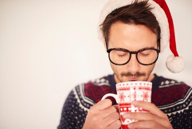 Mann mit weihnachtsmütze, die heiße praline trinkt