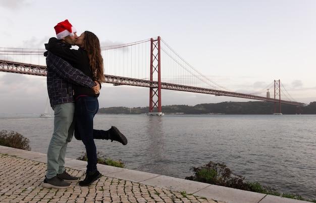 Mann mit weihnachtsmütze und frau küssen von brücke 25 de abril in lissabon portugal tourismuskonzept