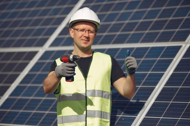 Mann mit weißem sturzhelm nahe einem sonnenkollektor