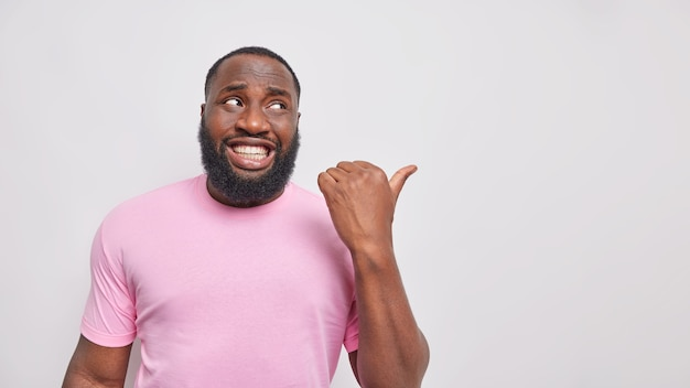 Mann mit weißen zähnen zeigt daumen weg auf leerzeichen zeigt platz für logo oder produktplatzierung in einem lässigen rosa t-shirt