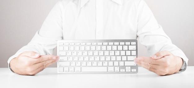 Mann mit weißer tastatur des computers oder des laptops
