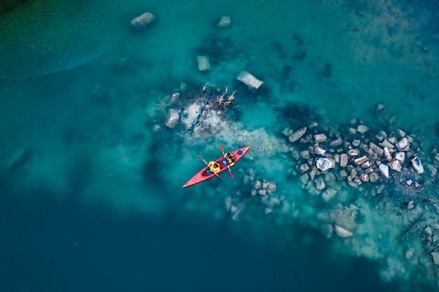 Mann mit zwei athleten schwimmt auf ein rotes boot im fluss