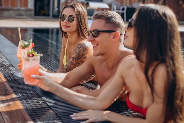 Mann mit zwei frauen am pool, die cocktails trinken und spaß am pool haben