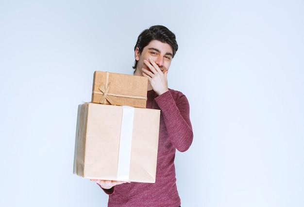 Mann mit zwei pappgeschenkboxen lächelnd.