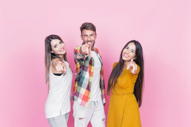Mann mit zwei weiblichen freunden, die vorwärts finger gegen rosa hintergrund zeigen