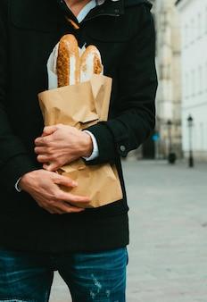 Mann mittleren alters auf der straße mit brot, baguette, broteinkauf während der globalen pandemie, maske tragen, brot aus der bäckerei holen. essen zum mitnehmen, bäckereieinkauf während covid 19.