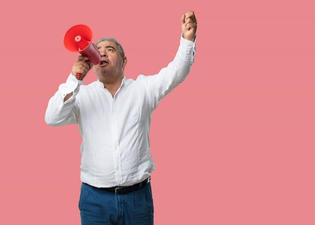 Mann mittleren alters, aufgeregt und euphorisch, mit megaphon schreiend, zeichen der revolution und ch