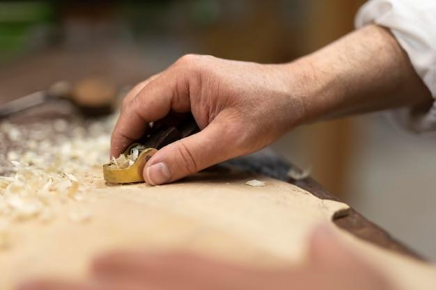 Mann mittleren alters, der allein in seiner werkstatt instrumente herstellt