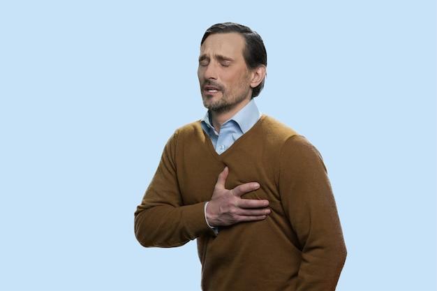 Mann mittleren alters, der an herzschmerz leidet. charmanter kaukasischer mann mit herzkrankheit, der seine brust berührt. auf blauem hintergrund isoliert.