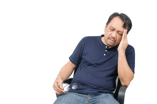 Mann mittleren alters, der auf stuhl sitzt und sich gestresst und kopfschmerzen lokalisiert auf weißem hintergrund fühlt. problem- und gesundheitskonzept.
