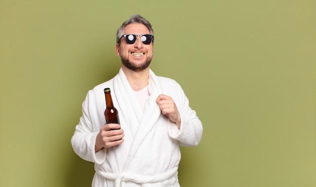 Mann mittleren alters, der bademantel trägt und ein bier trinkt
