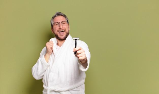 Mann mittleren alters, der bademantel und ein rasiermesser trägt