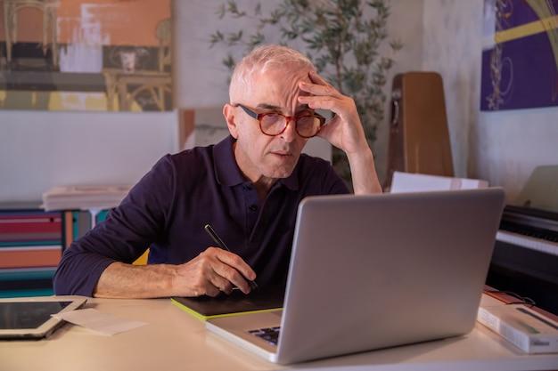 Mann mittleren alters, der computer in seinem kunststudio verwendet und auf seine tablette zeichnet