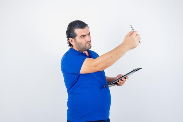 Mann mittleren alters, der durch bleistift schaut, während zwischenablage im polo-t-shirt hält und konzentriert schaut. vorderansicht.