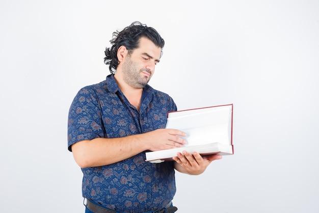 Mann mittleren alters, der durch buch im hemd schaut und fokussierte vorderansicht schaut.
