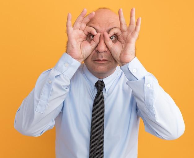 Mann mittleren alters, der ein weißes t-shirt mit krawatte trägt und eine geste zeigt, die auf orangefarbener wand isoliert ist?