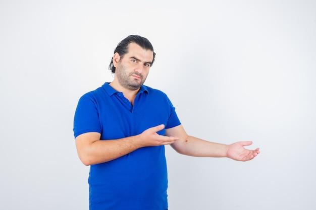 Mann mittleren alters, der etwas im blauen t-shirt begrüßt und selbstbewusst aussieht. vorderansicht.