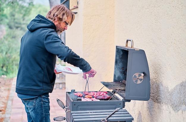 Mann mittleren alters, der fleisch auf dem grill im hinterhof des hauses kocht
