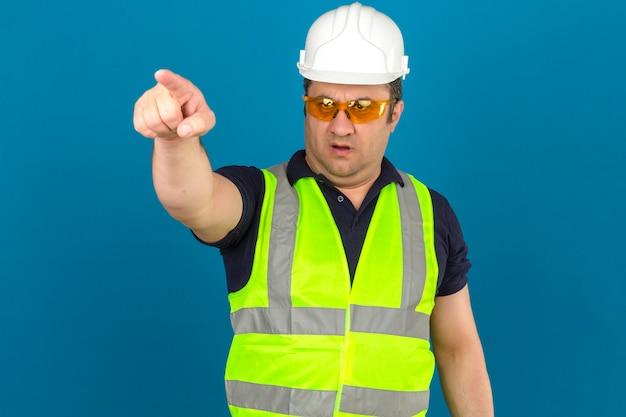 Mann mittleren alters, der gelbe weste der konstruktion und schutzhelm trägt, der auf etwas vor mit ernstem gesicht über isolierter blauer wand zeigt