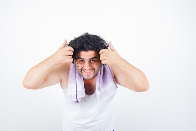 Mann mittleren alters, der haarsträhne hält, während kamera in tank top, handtuch und glücklich, vorderansicht betrachtet.