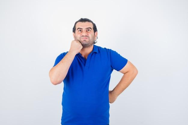 Mann mittleren alters, der im blauen t-shirt oben schaut und nachdenklich schaut. vorderansicht.