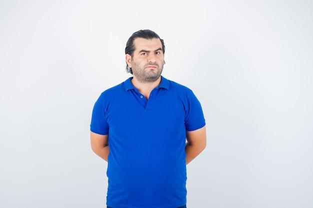 Mann mittleren alters, der kamera betrachtet, während hände hinten in blauem t-shirt zurückhält und selbstbewusste vorderansicht schaut.