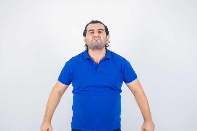 Mann mittleren alters, der kamera im blauen t-shirt betrachtet und ernst schaut. vorderansicht.
