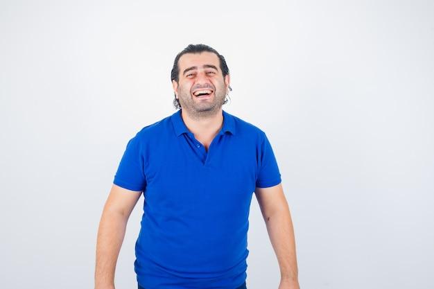 Mann mittleren alters, der kamera im blauen t-shirt betrachtet und freudige vorderansicht schaut.