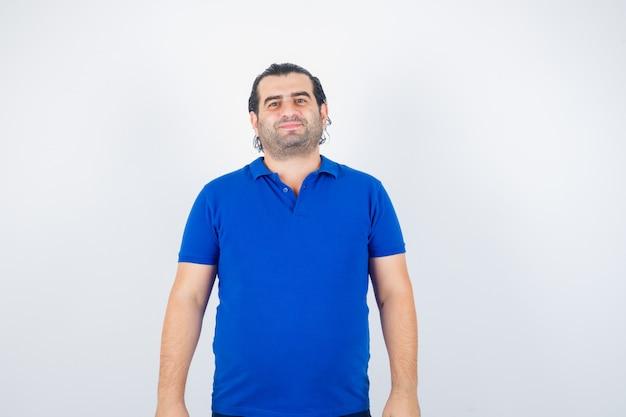 Mann mittleren alters, der kamera im blauen t-shirt betrachtet und glücklich schaut. vorderansicht.
