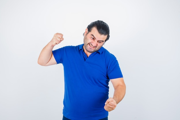 Mann mittleren alters, der kampfhaltung im polo-t-shirt zeigt und gereizt aussieht. vorderansicht.