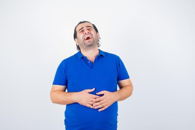 Mann mittleren alters, der lacht, während er hände auf bauch im blauen t-shirt hält und fröhlich schaut. vorderansicht.
