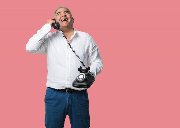 Mann mittleren alters, der laut lacht, spaß mit dem gespräch hat und einen freund oder einen kunden anruft