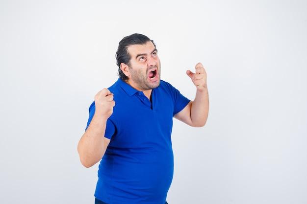 Mann mittleren alters, der mit fäusten im polo-t-shirt droht und wütend schaut, vorderansicht.