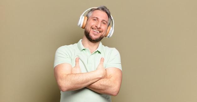 Mann mittleren alters, der musik mit seinen kopfhörern hört