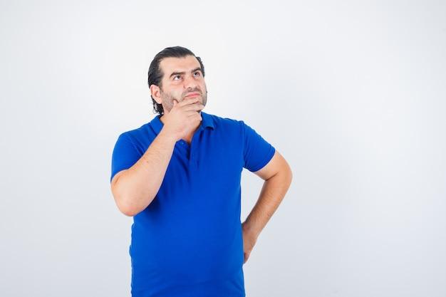 Mann mittleren alters, der nach oben schaut, während er hand auf hüfte im blauen t-shirt hält und nachdenklich, vorderansicht schaut.