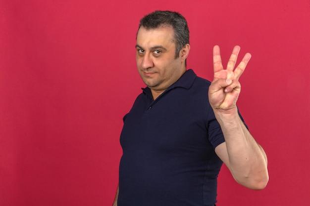Mann mittleren alters, der poloshirt mit lächeln auf gesicht trägt und nummer drei mit den fingern über isolierter rosa wand zeigt