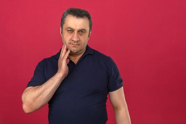 Mann mittleren alters, der poloshirt trägt, das kinn berührt, während mit ernstem gesicht über isolierte rosa wand denkt