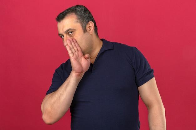 Mann mittleren alters, der poloshirt trägt, flüstert ein geheimnis, das seinen mund mit seiner hand über isolierter rosa wand bedeckt