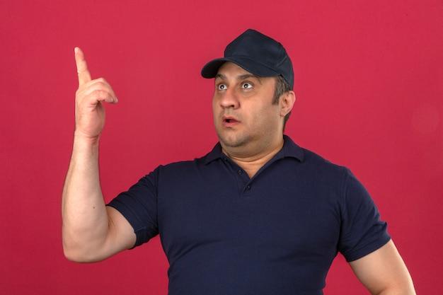Mann mittleren alters, der poloshirt und kappe trägt, die oben mit dem finger zeigen, der über isolierte rosa wand überrascht schaut