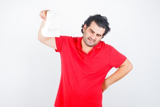 Mann mittleren alters, der serviette anhebt, während hand auf hüfte im roten t-shirt hält und nachdenklich, vorderansicht schaut.