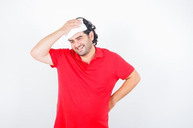 Mann mittleren alters, der serviette auf kopf hält, während hand auf hüfte im roten t-shirt hält und glückliche vorderansicht schaut.