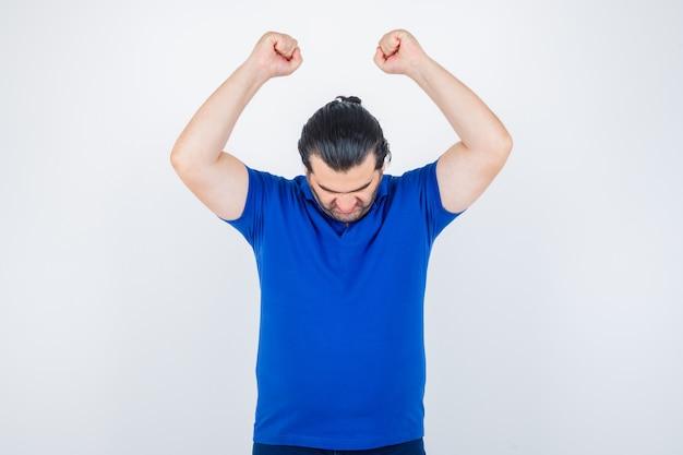 Mann mittleren alters, der siegergeste im blauen t-shirt zeigt und glücklich schaut. vorderansicht.
