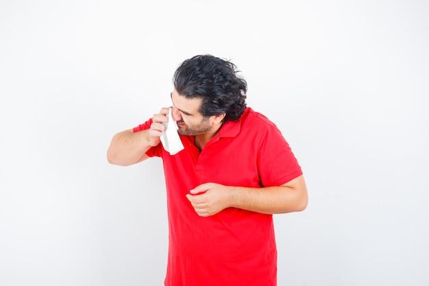 Mann mittleren alters, der taschentuch hält, das laufende nase im roten t-shirt bläst und ungesunde vorderansicht schaut.