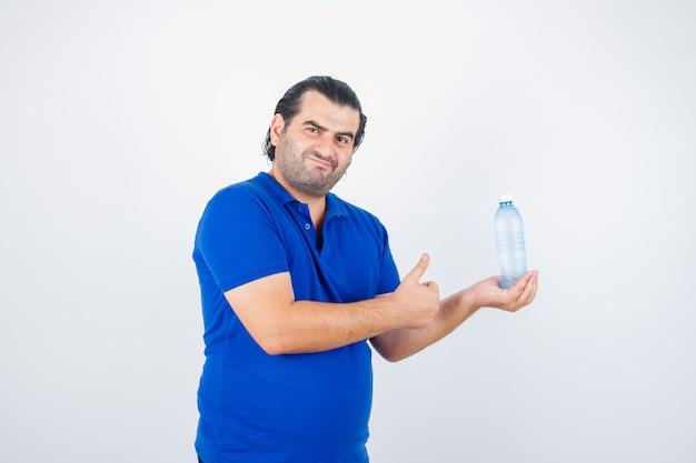 Mann mittleren alters, der wasserflasche hält, während daumen oben im polo-t-shirt zeigt und zufrieden schaut, vorderansicht.