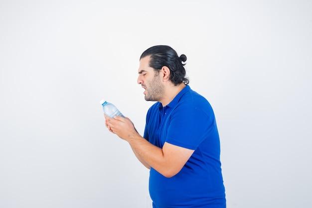 Mann mittleren alters, der wasserflasche im blauen t-shirt betrachtet und wütend schaut. vorderansicht.