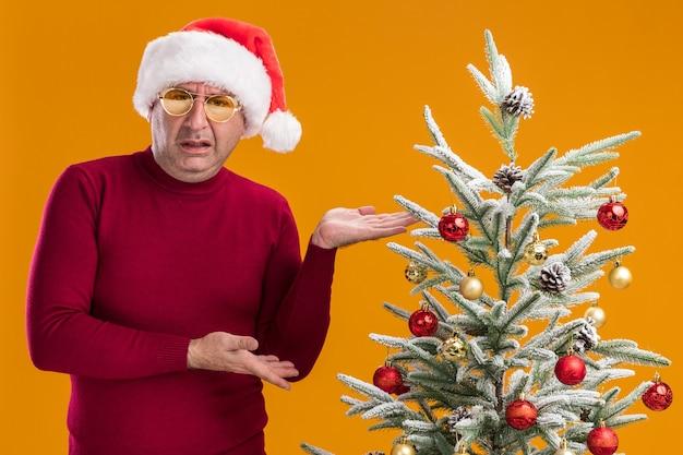 Mann mittleren alters, der weihnachtsmütze des weihnachtsmanns im dunkelroten rollkragenpullover und in der gelben brille trägt, die neben einem weihnachtsbaum stehen, der mit armen präsentiert, die verwirrt und unzufrieden über orange hintergrund schauen